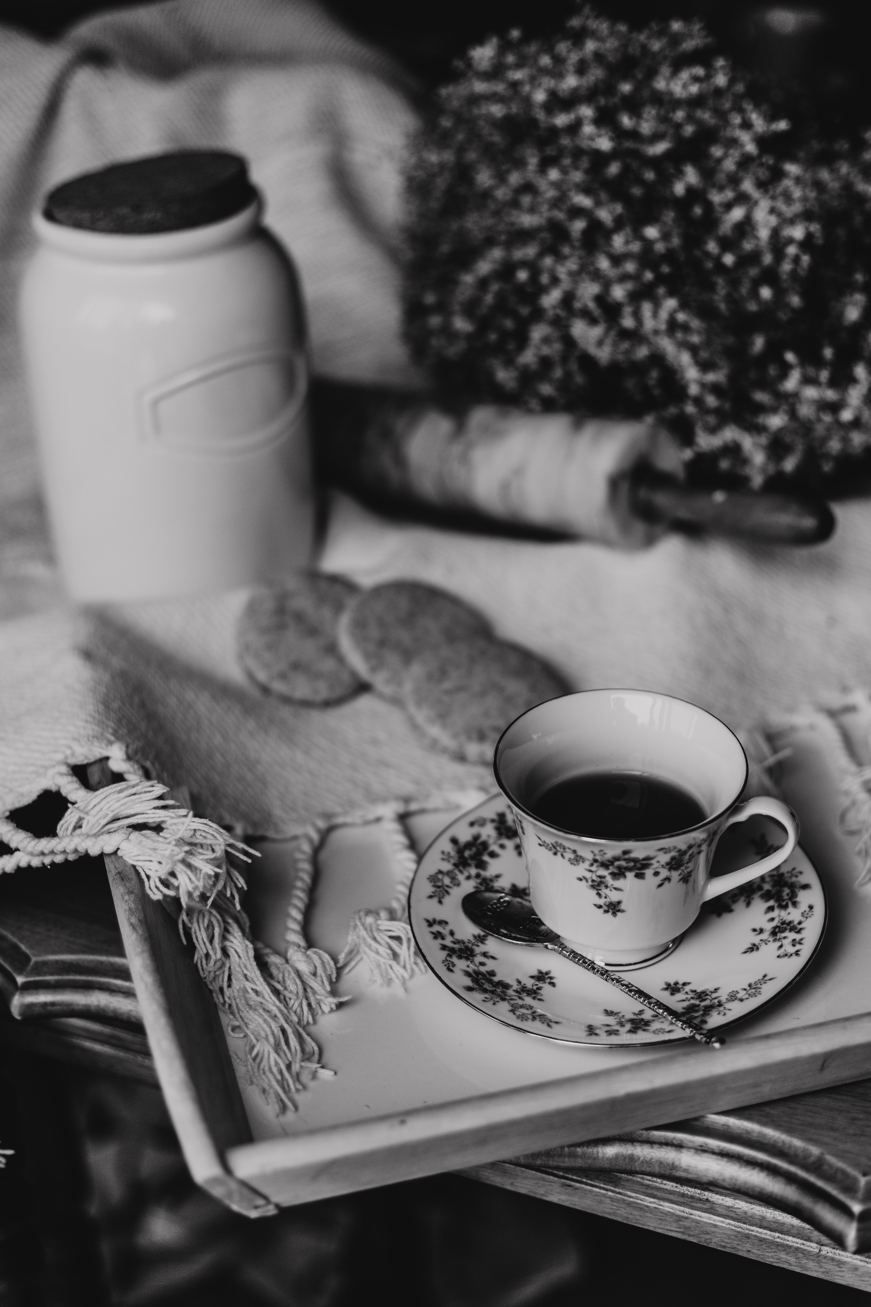 grayscale photography of teacup on a tray near cookies and jar