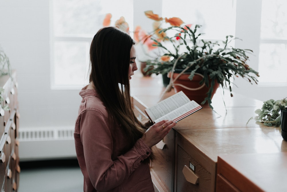 woman reading a book in front of brown wooden drawer