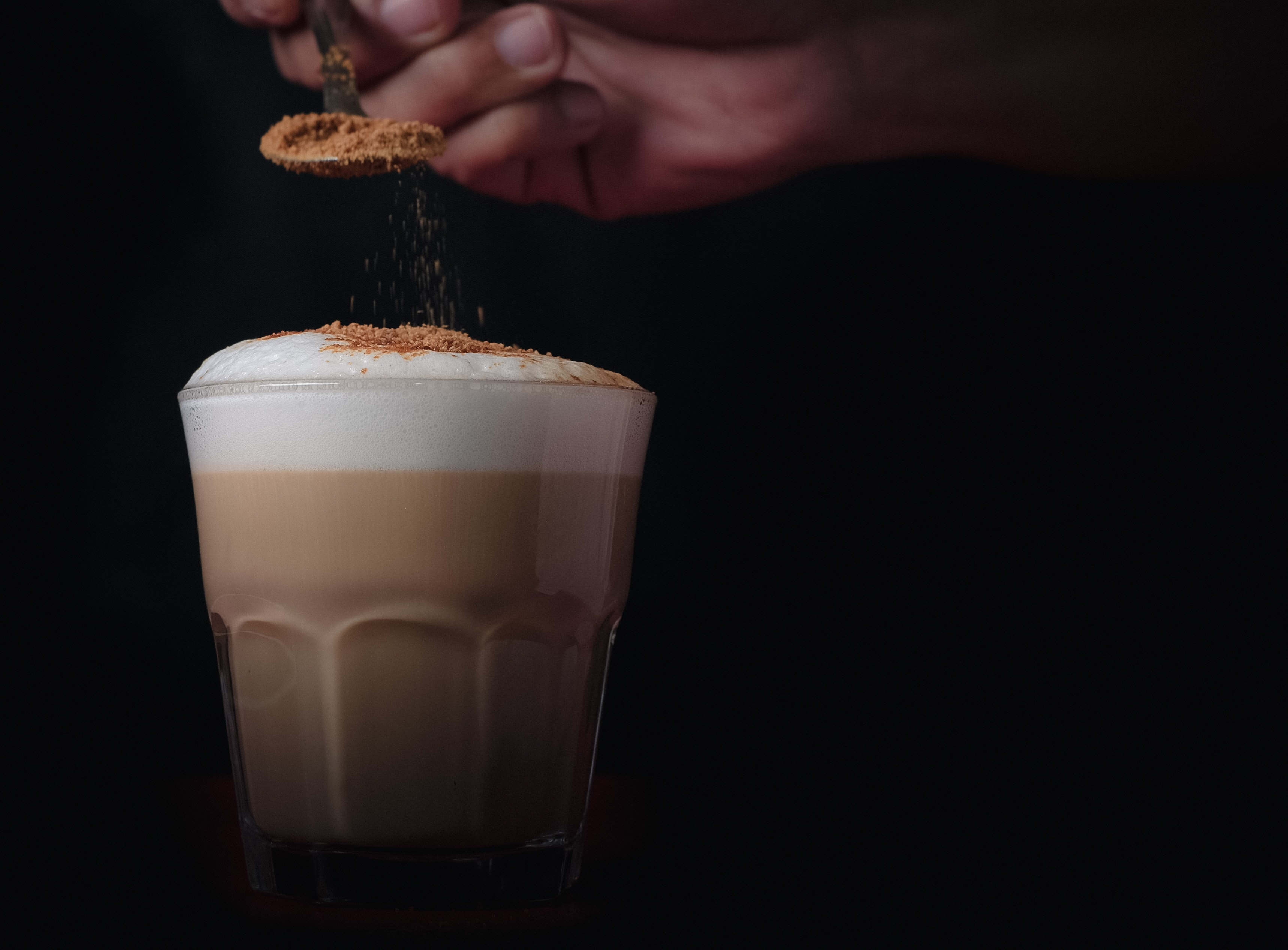 person holding spoon pouring powder on coffee