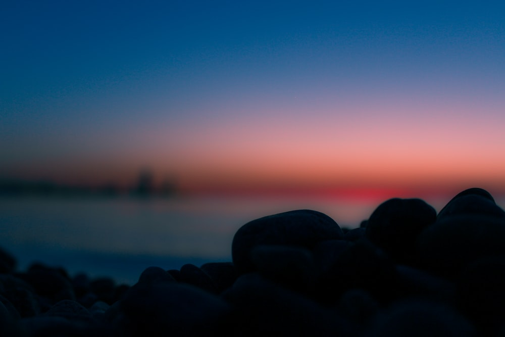silhouette of rock near the body of water