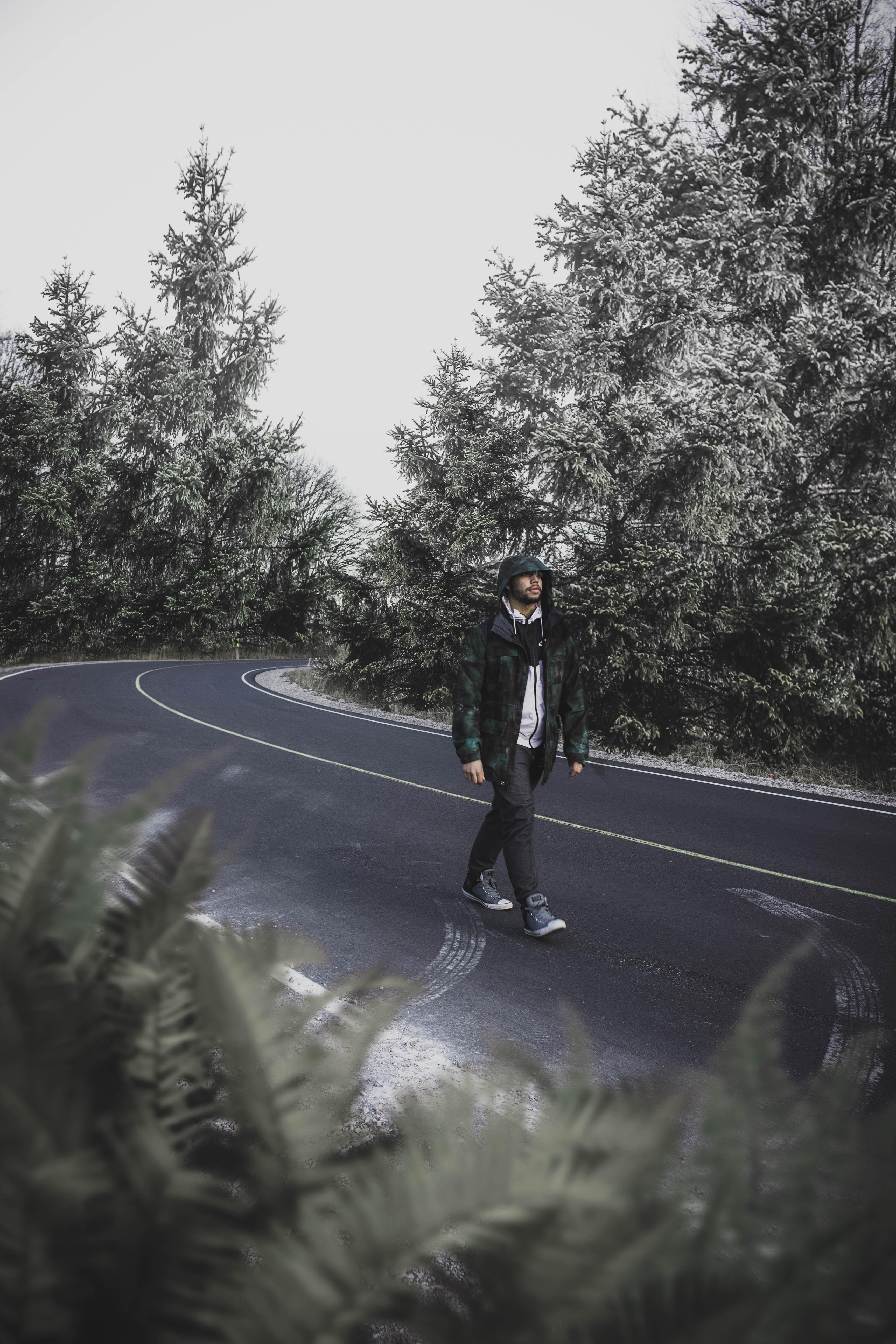 man walking on street between trees