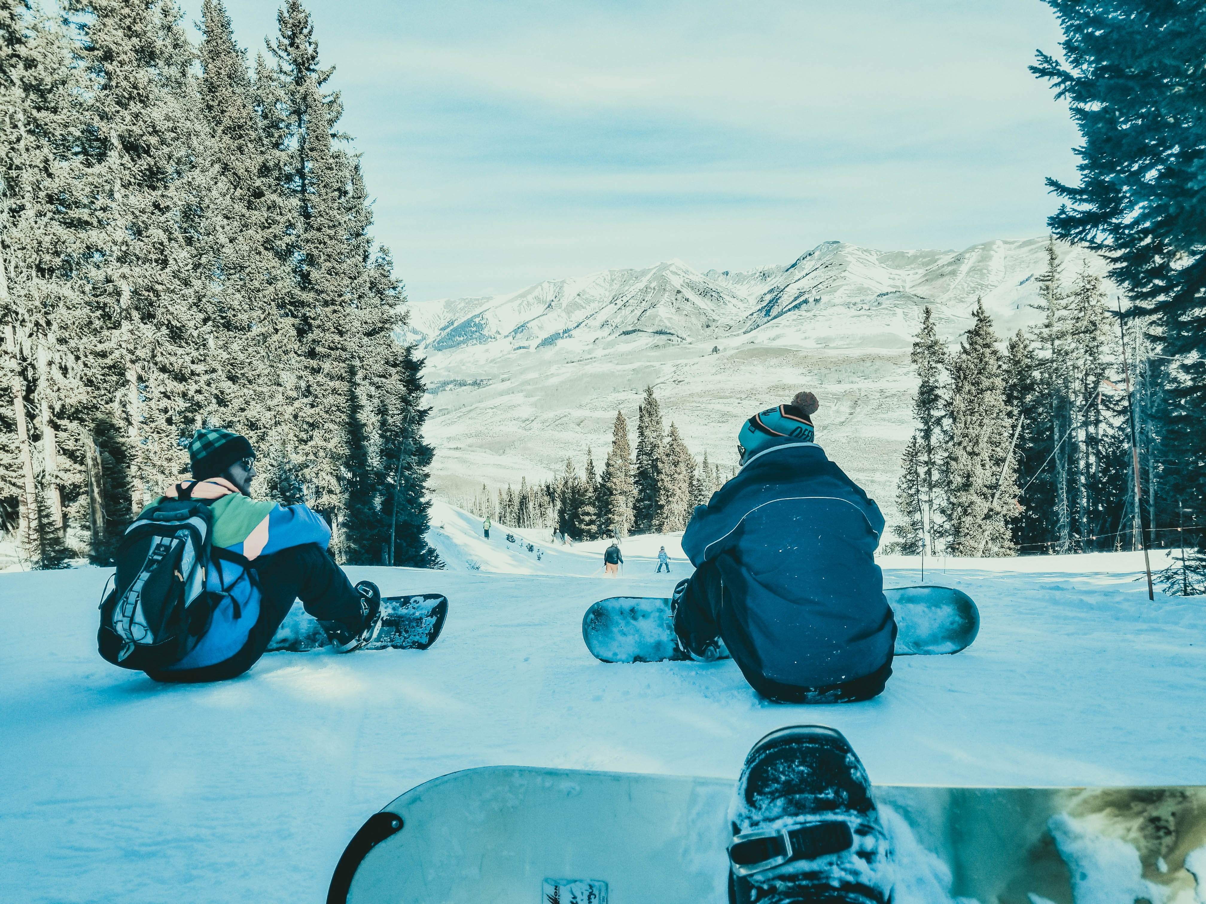 two persons sitting on snow with their snowboards
