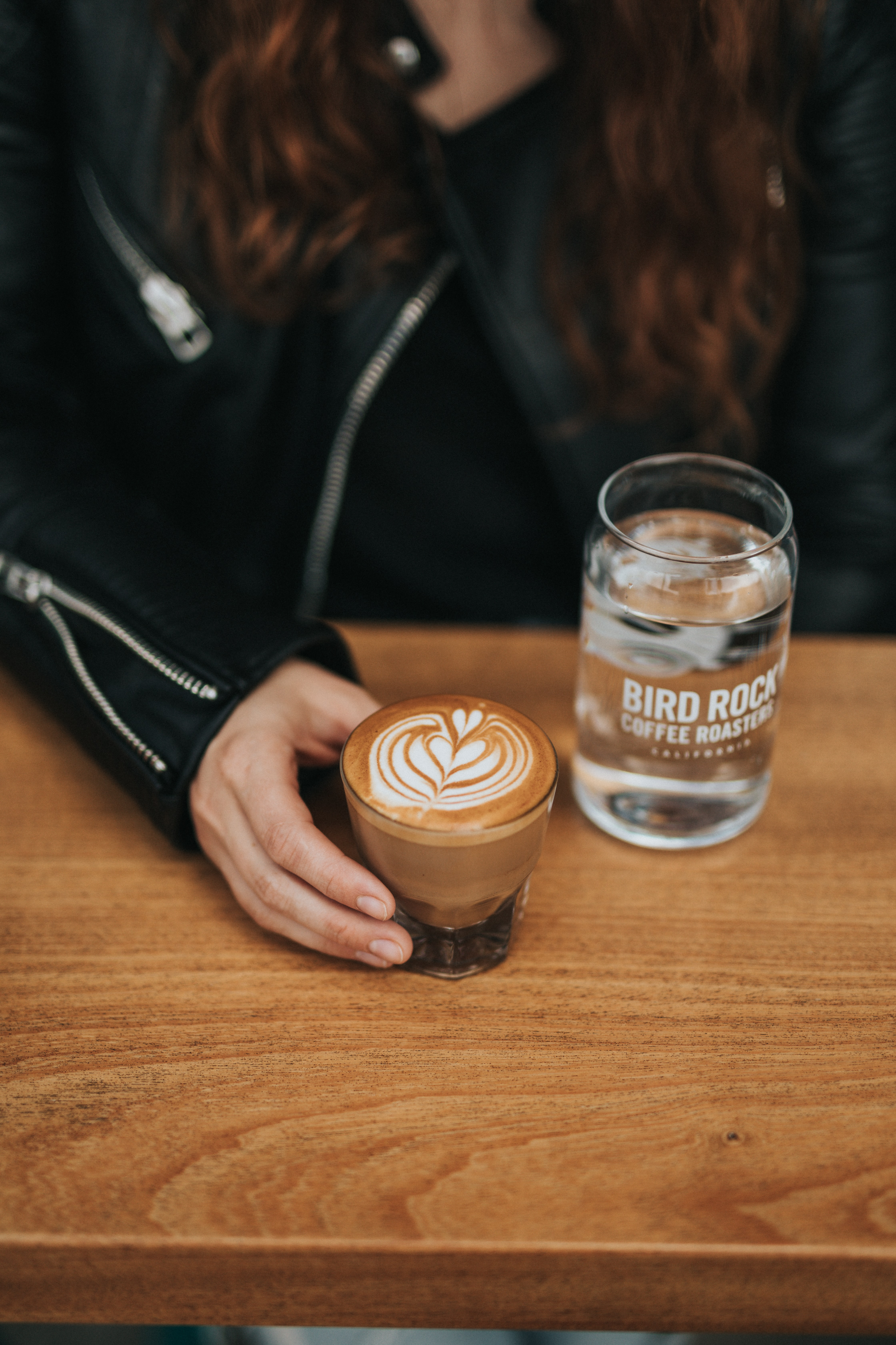 woman holding a glass of cappuccino beside glass of water on the table