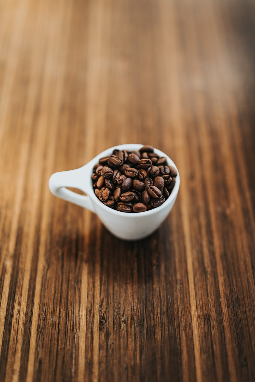 round white ceramic mug with coffee beans