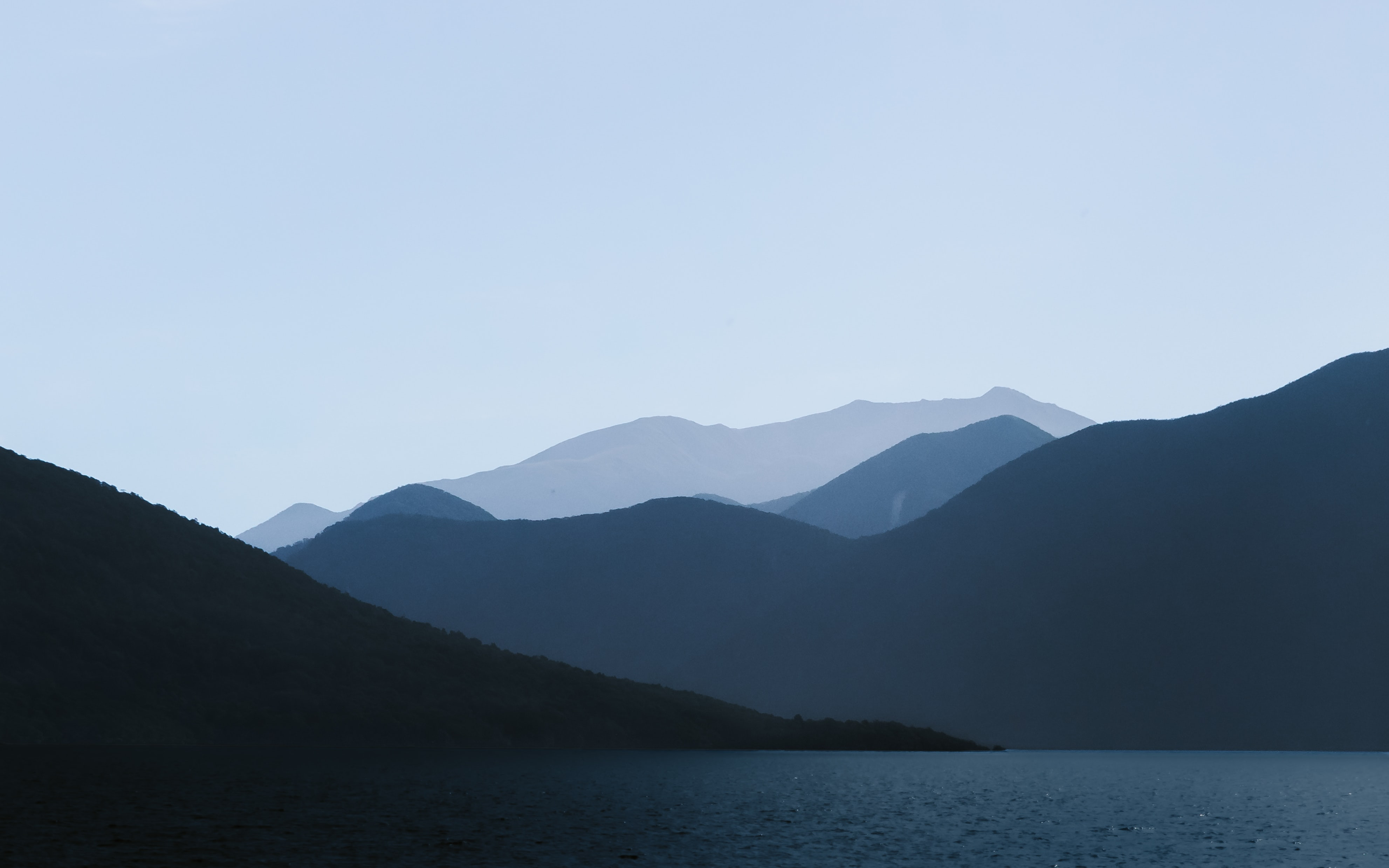 selective focus photography of mountain near water