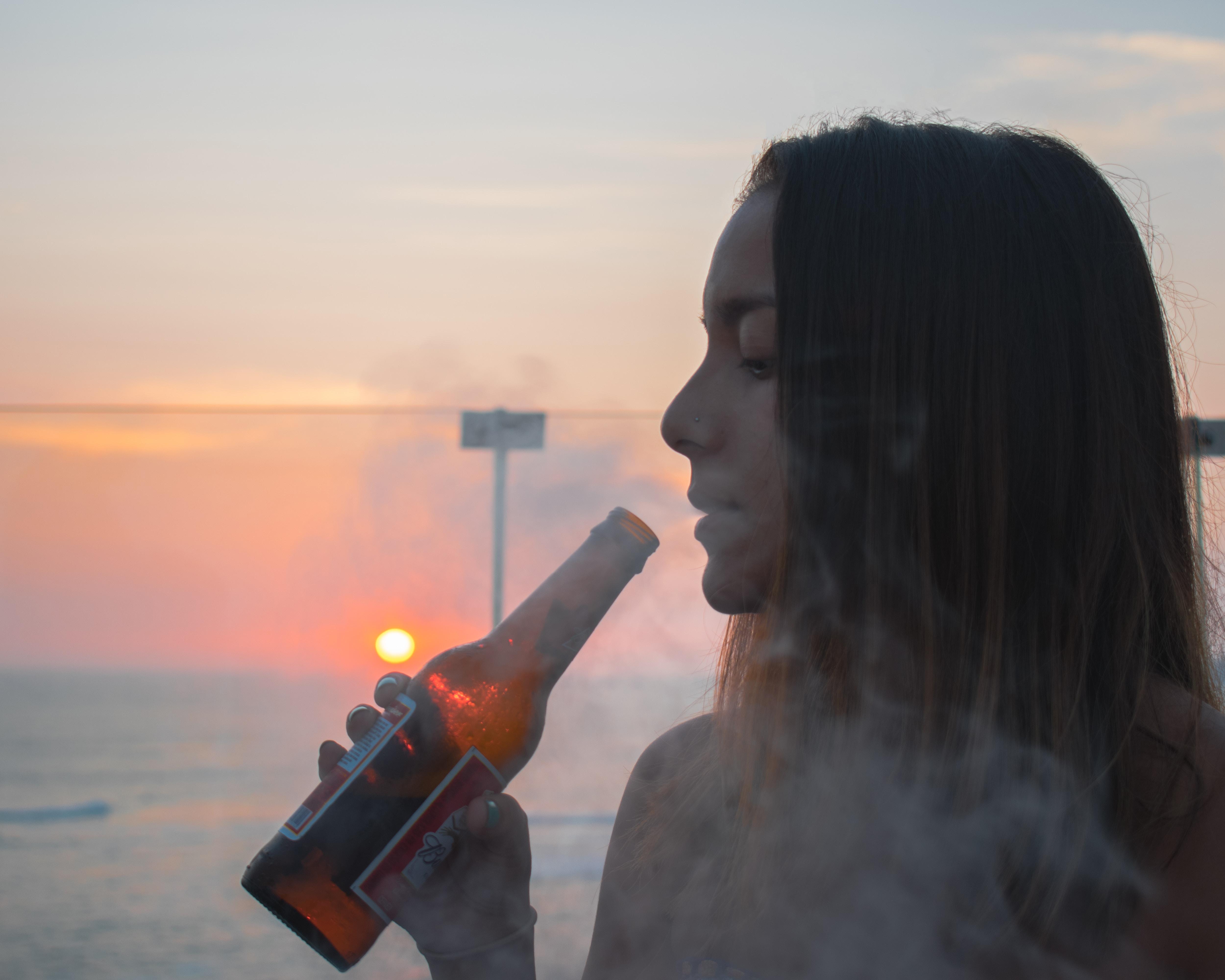 woman blowing smoke in brown bottle