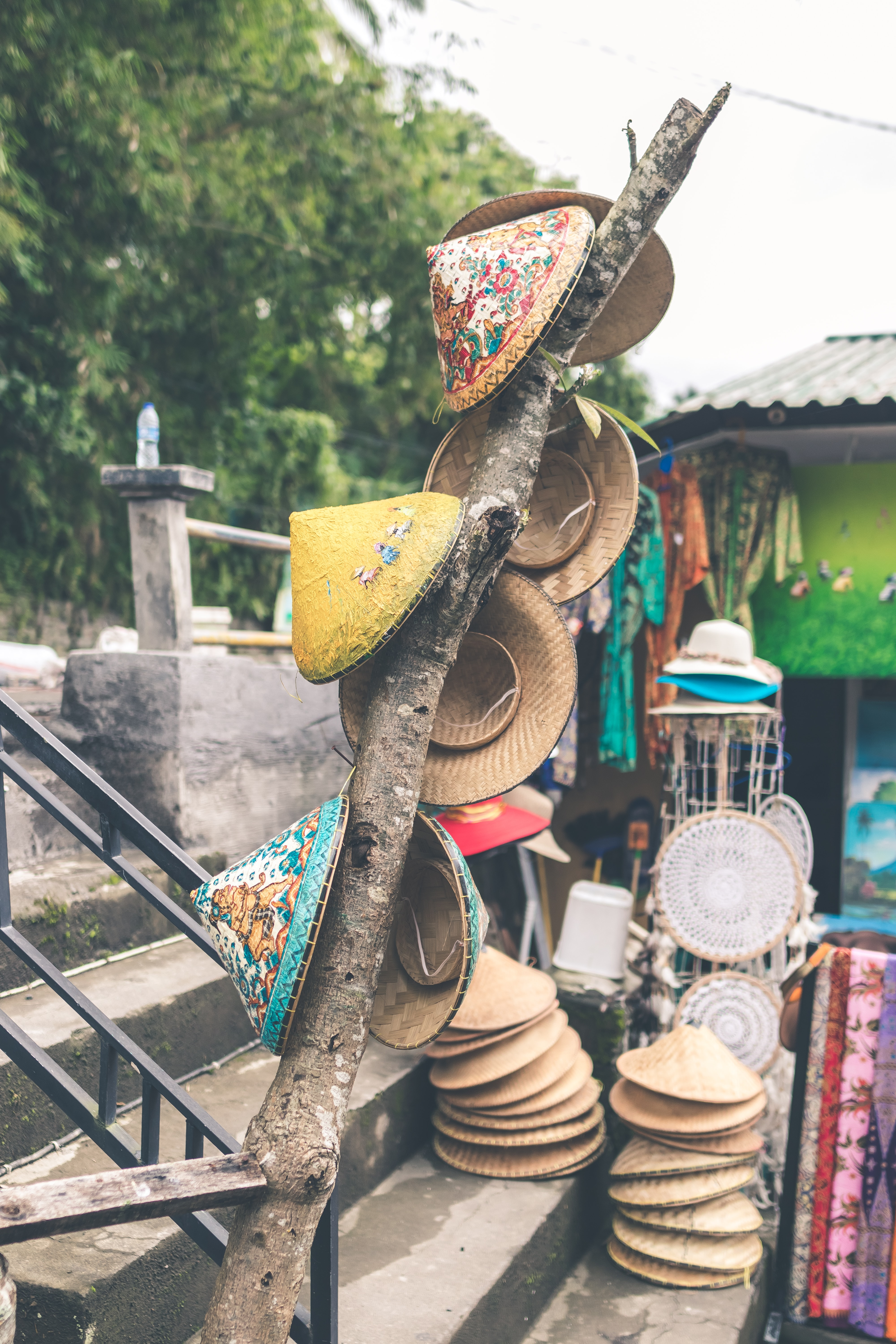 assorted-color straw hats on concrete stair
