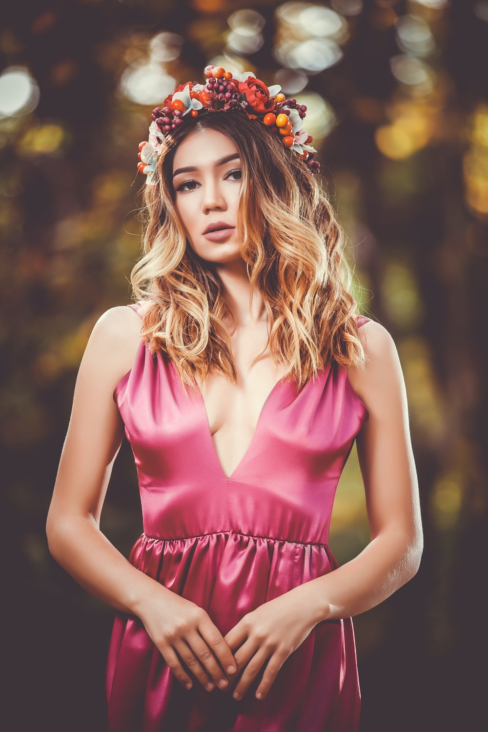 woman in pink V-neck sleeveless dress wearing flower crown in bokeh photography