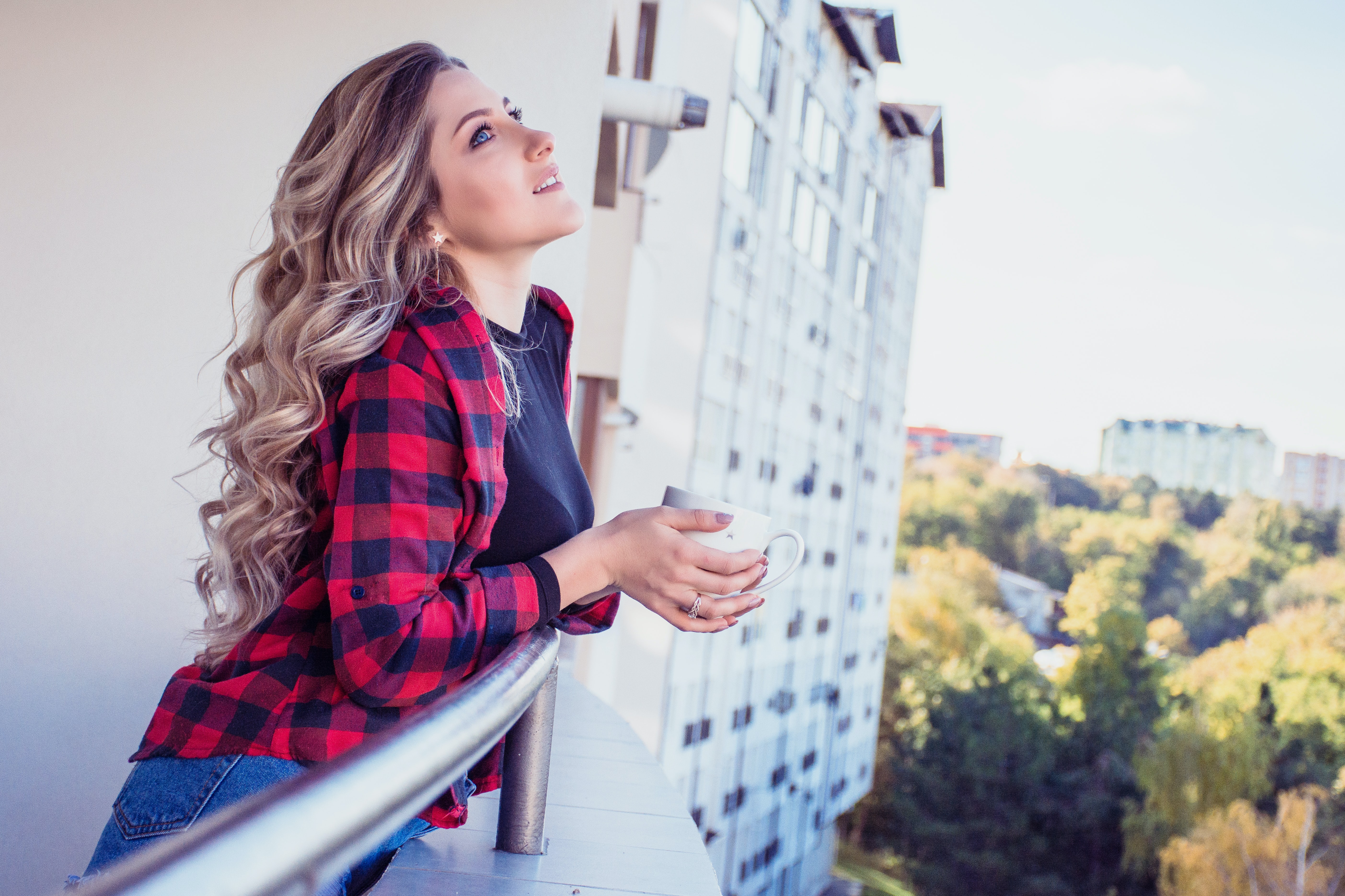 woman looking up while leaning on balcony of a building