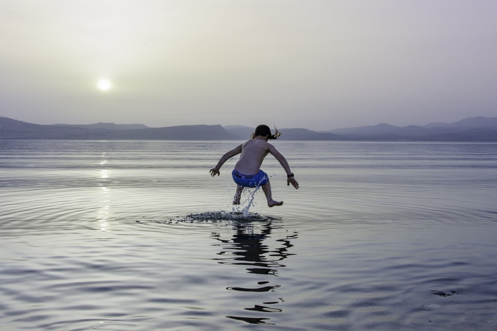 time lapse photography of girl jumping on water