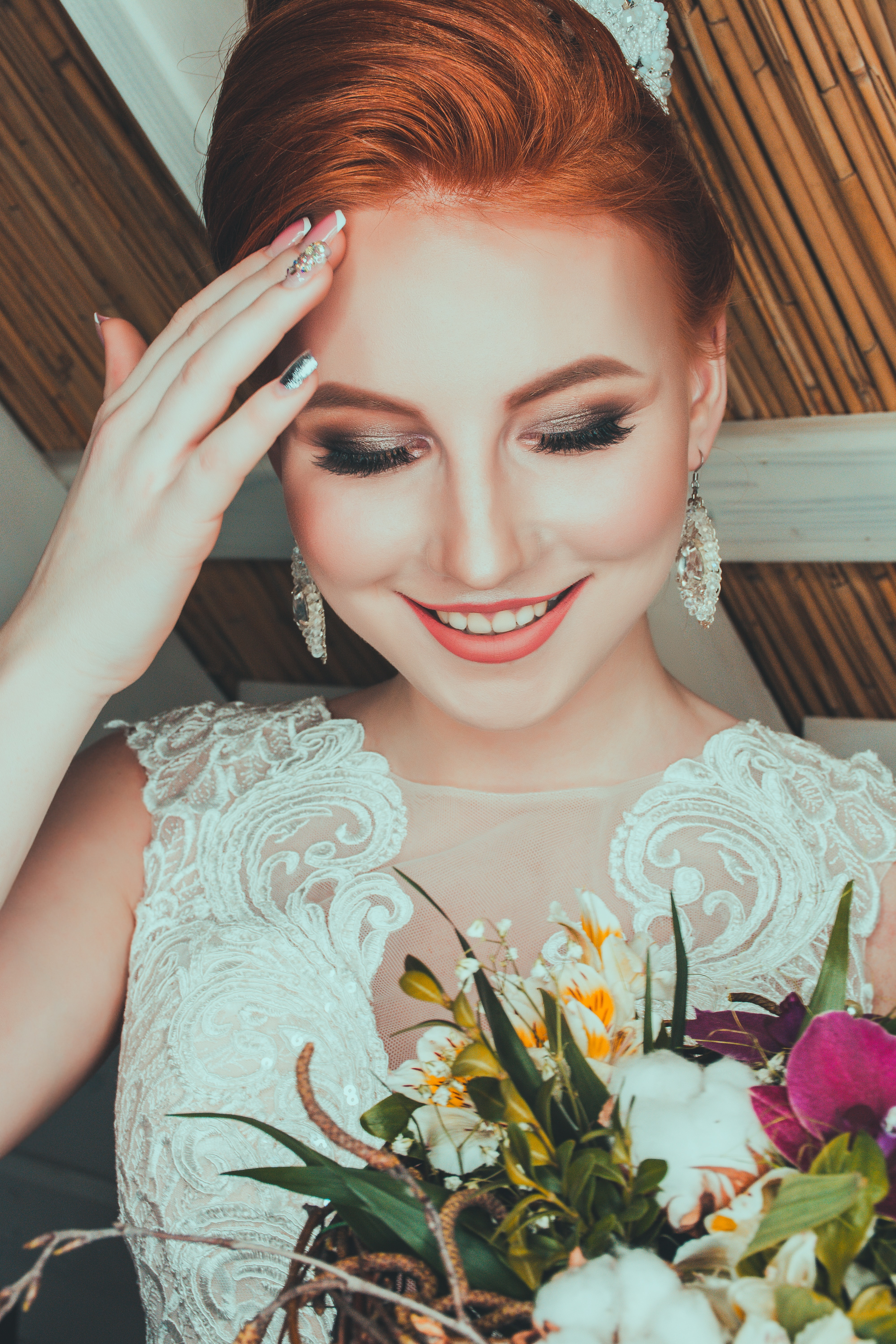 woman wearing bridal gown touching her forehead