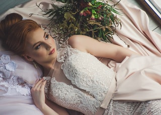 woman in dress lying on bed near window