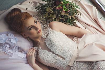 woman in dress lying on bed near window bride zoom background