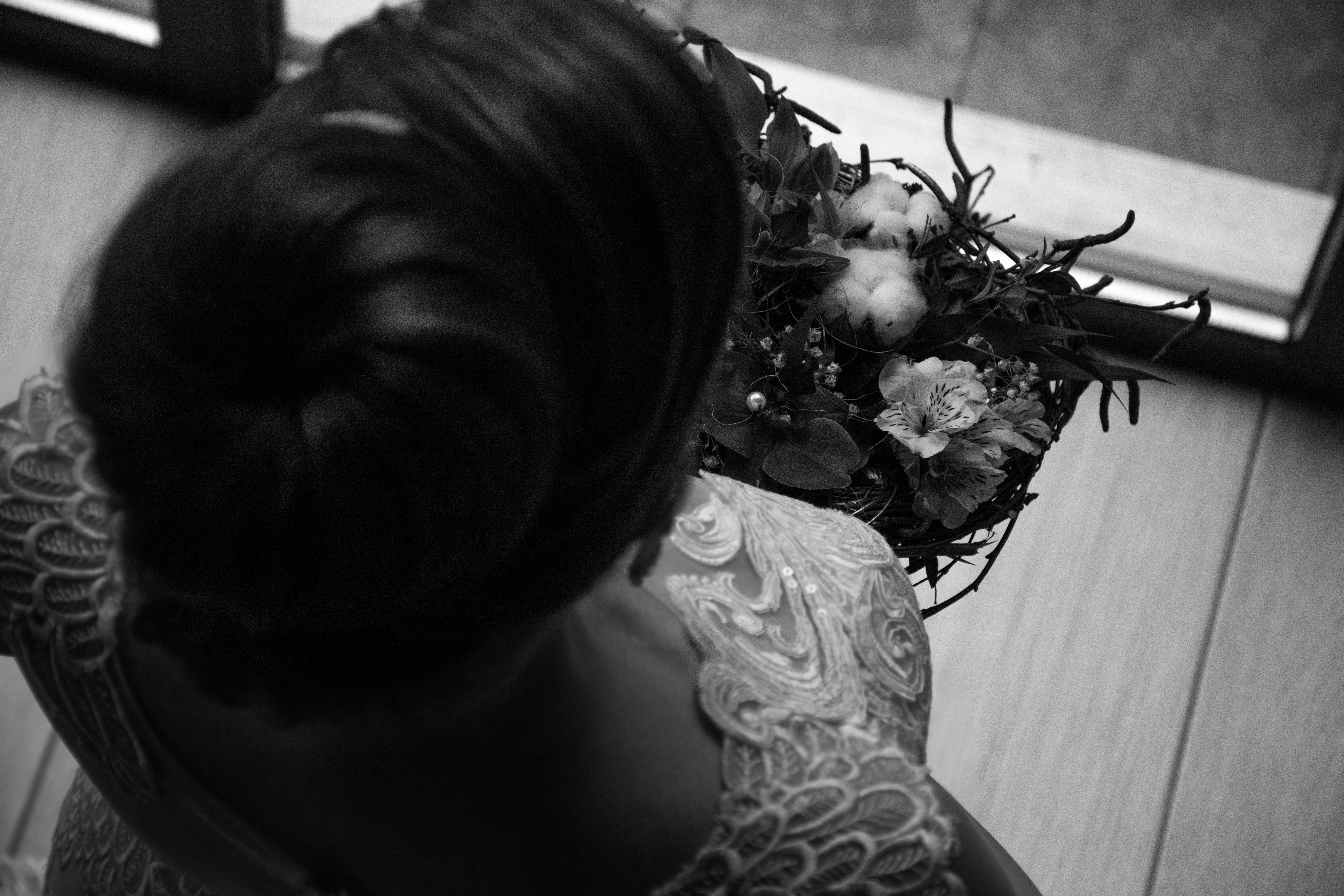 grayscale photo of woman holding flowers