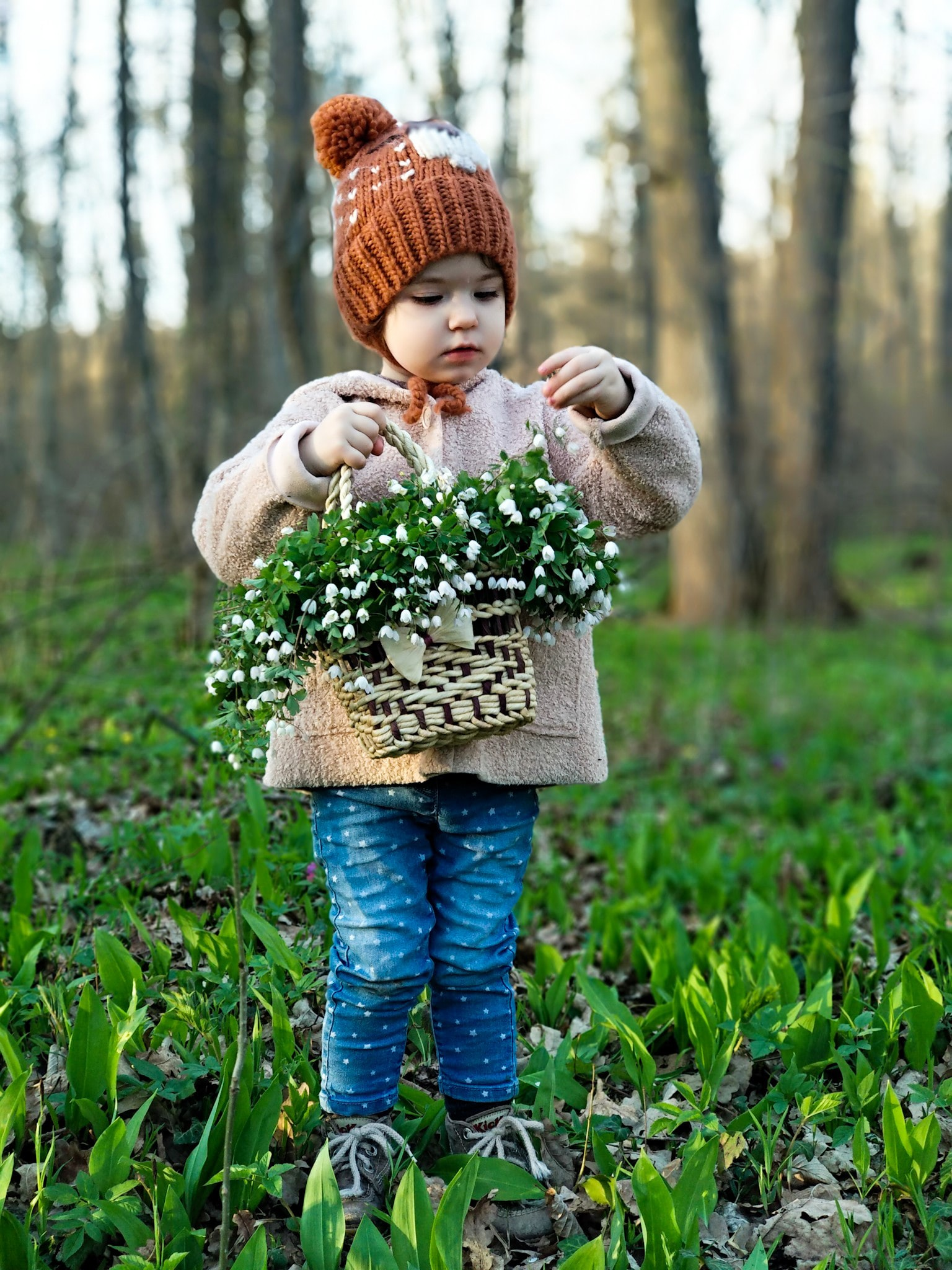 toddler girl holding basket full of flowers in forest