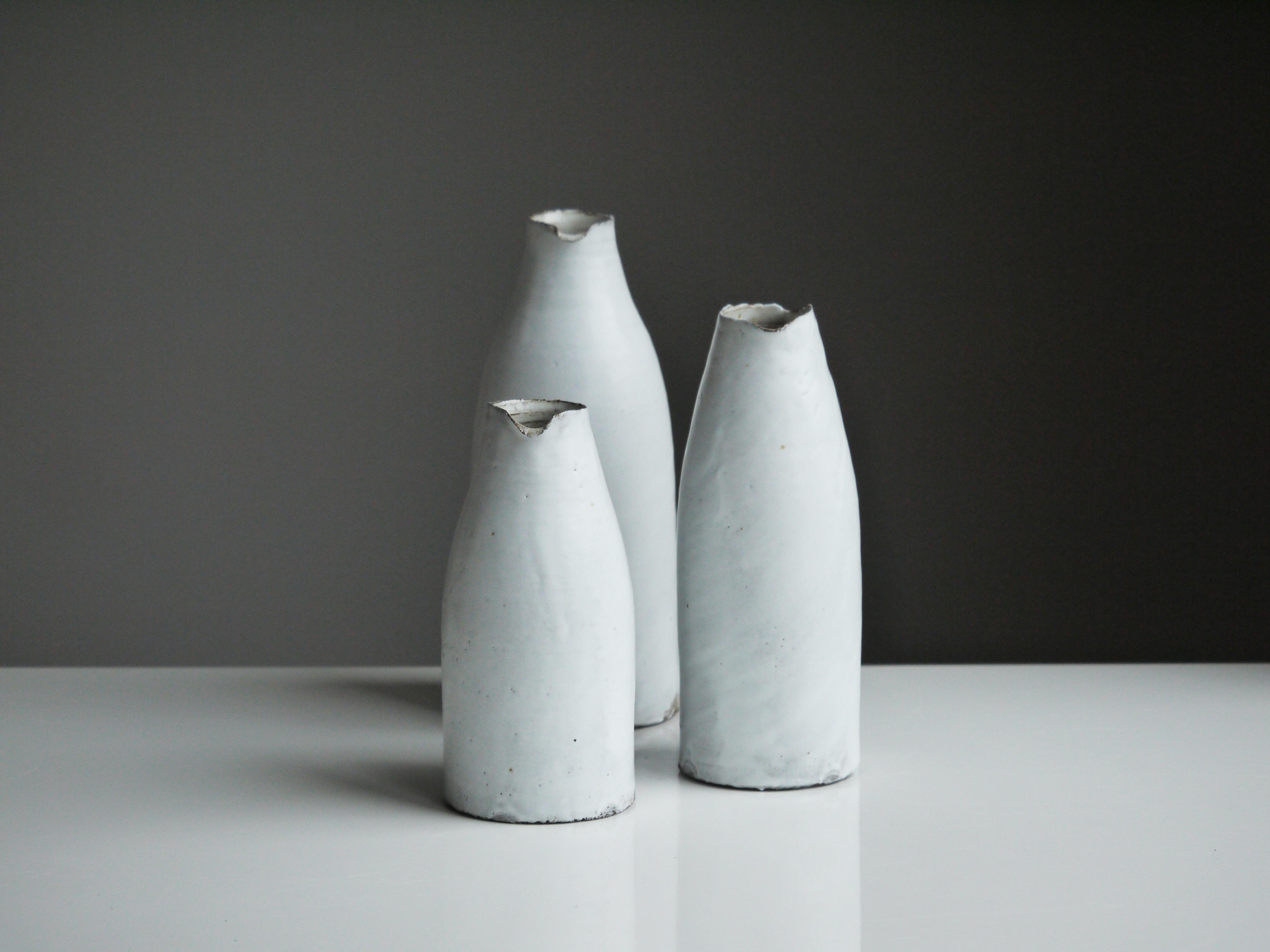three white vases on table