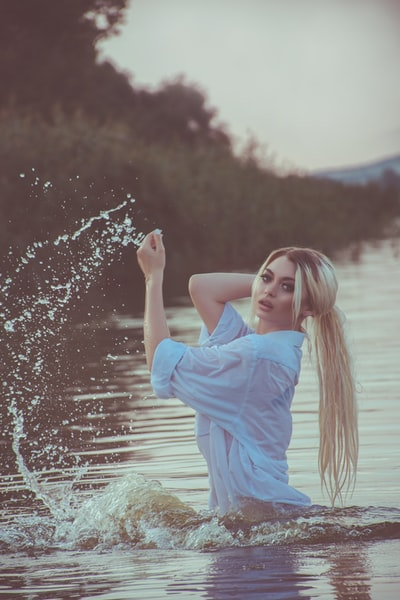 selective focus photo of woman on body of water holding her hair