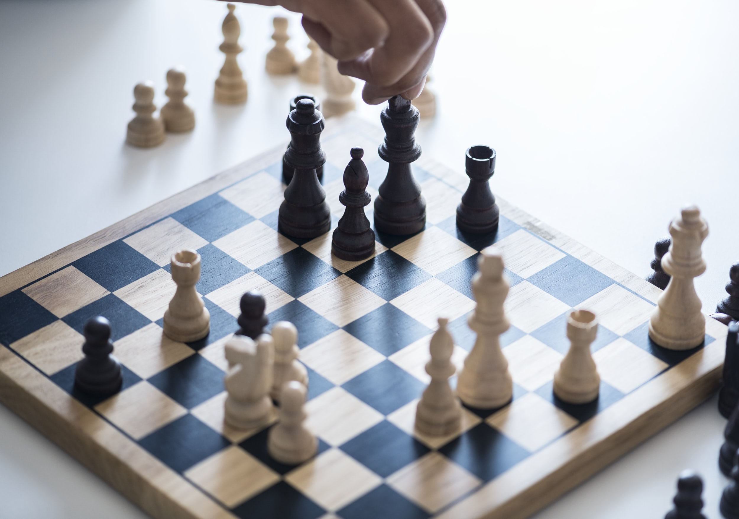 person making move on brown and black wooden chessboard with pieces