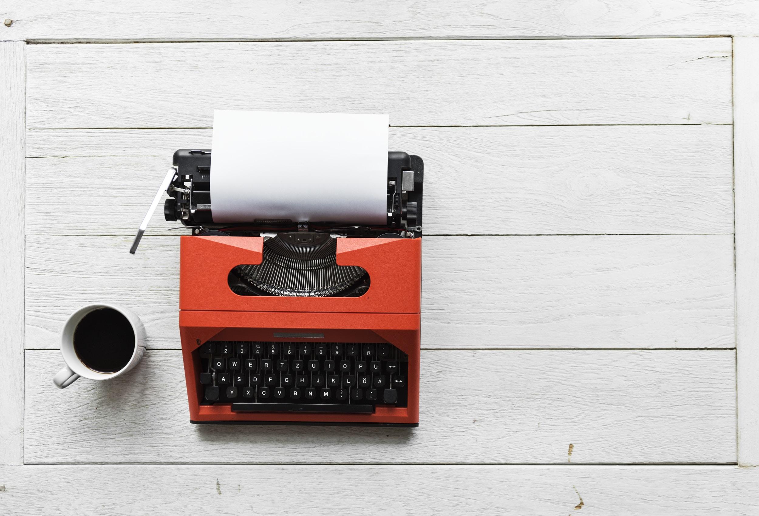red and black typewriter near white ceramic mug with coffee