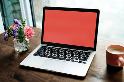 MacBook Pro on wooden surface between mug and flower arrangement