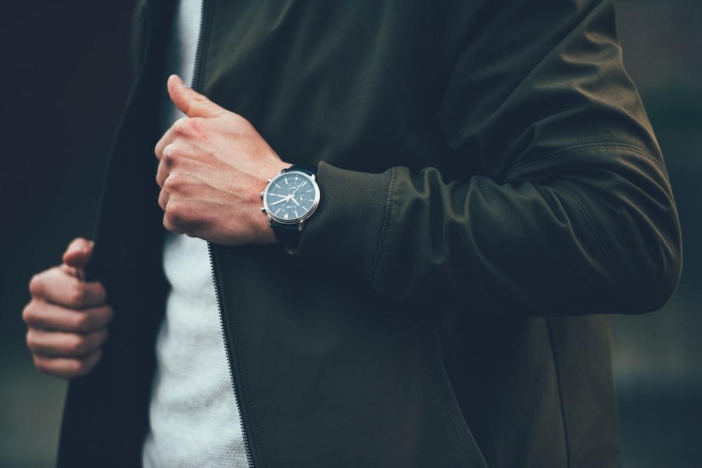 man wearing black jacket and holding it