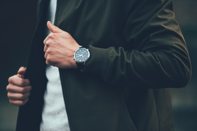 man wearing black jacket and holding it watch zoom background