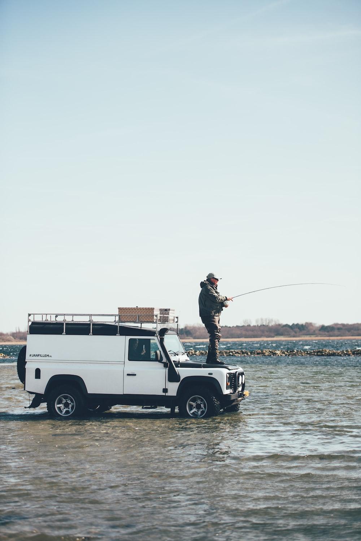man holding fishing rod on SUV hood\