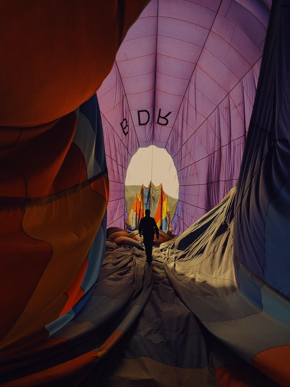 person walking inside purple tent tunnel