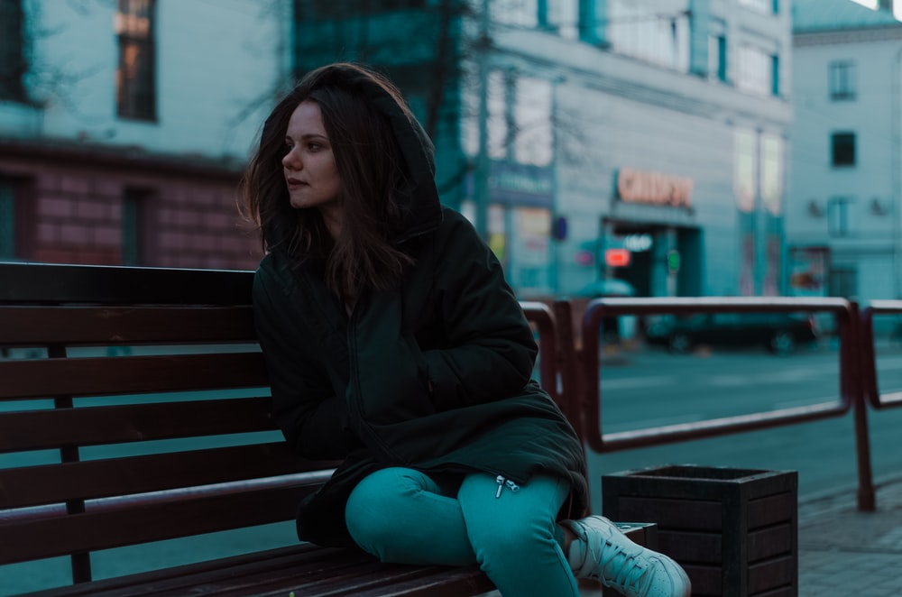 woman sitting on bench beside road