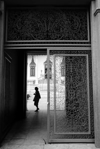 grayscale photography of person standing near hallway