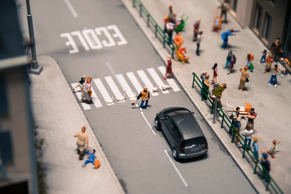 photo of people on sidewalk near building and car on pavement mini figures
