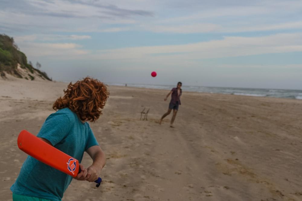 person holding red cricket bat near seashore