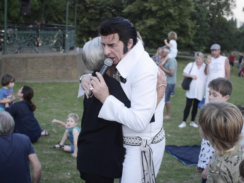 woman hugging man holding microphone