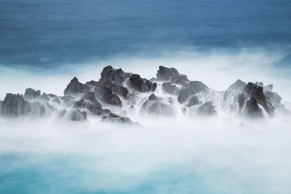 photo of sea waves hitting stones