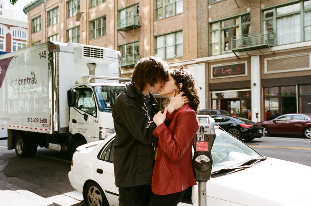 man kissing woman near white car