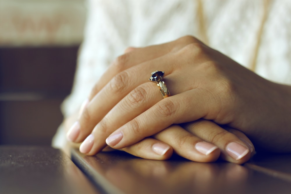 person wearing silver-colored ring with black gemstone