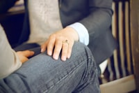 close-up photo of man in front of person sitting on chair