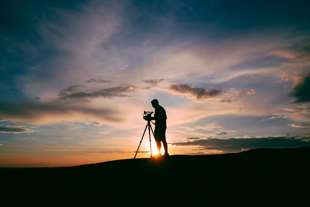 silhouette of man standing beside camera tripod during sunset