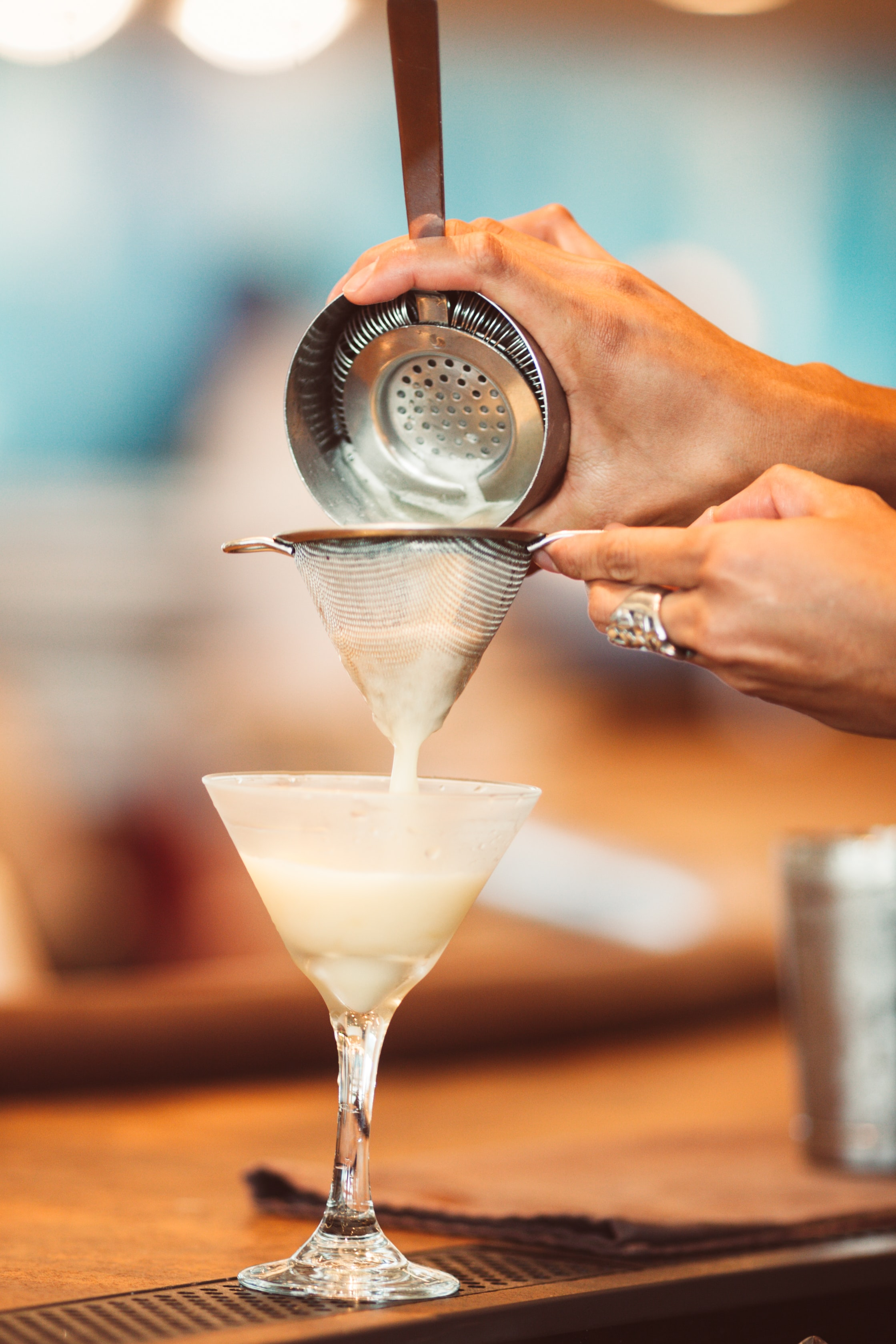 person holding container pouring white liquid on martini glass