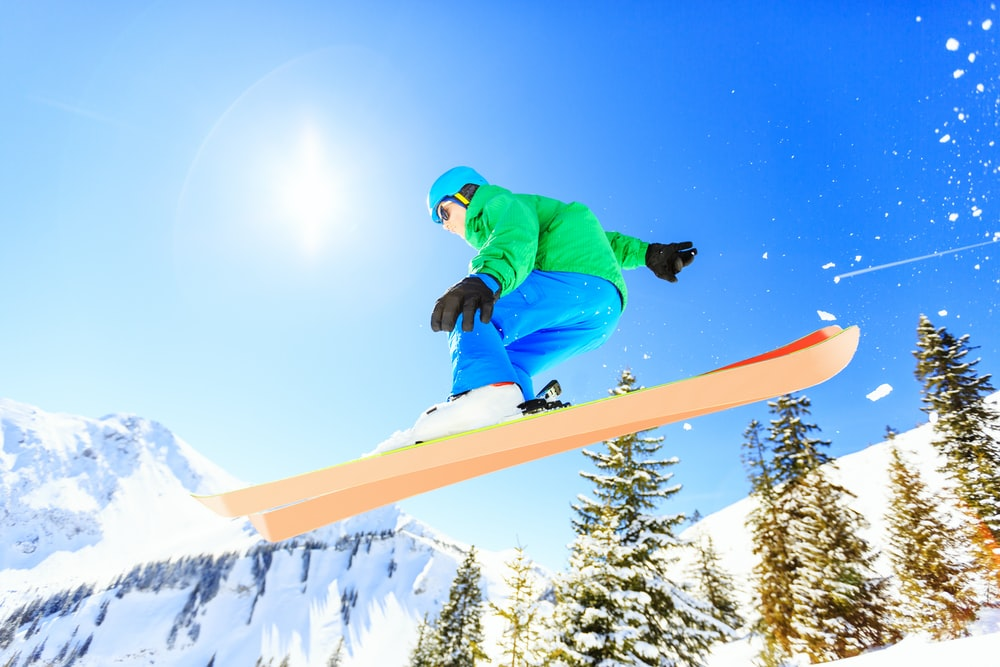 person wearing green jacket riding snow skis