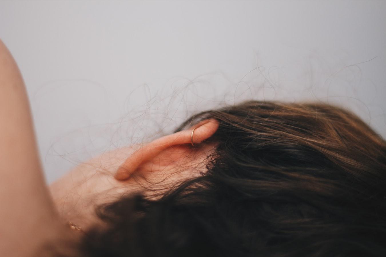 Hinterkopf einer Person mit braunem, langen Haar und Ohrpiercing