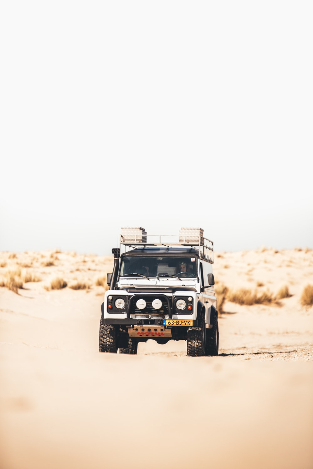 tilt shift photo of a white vehicle passing through sand dunes surrounded by grass