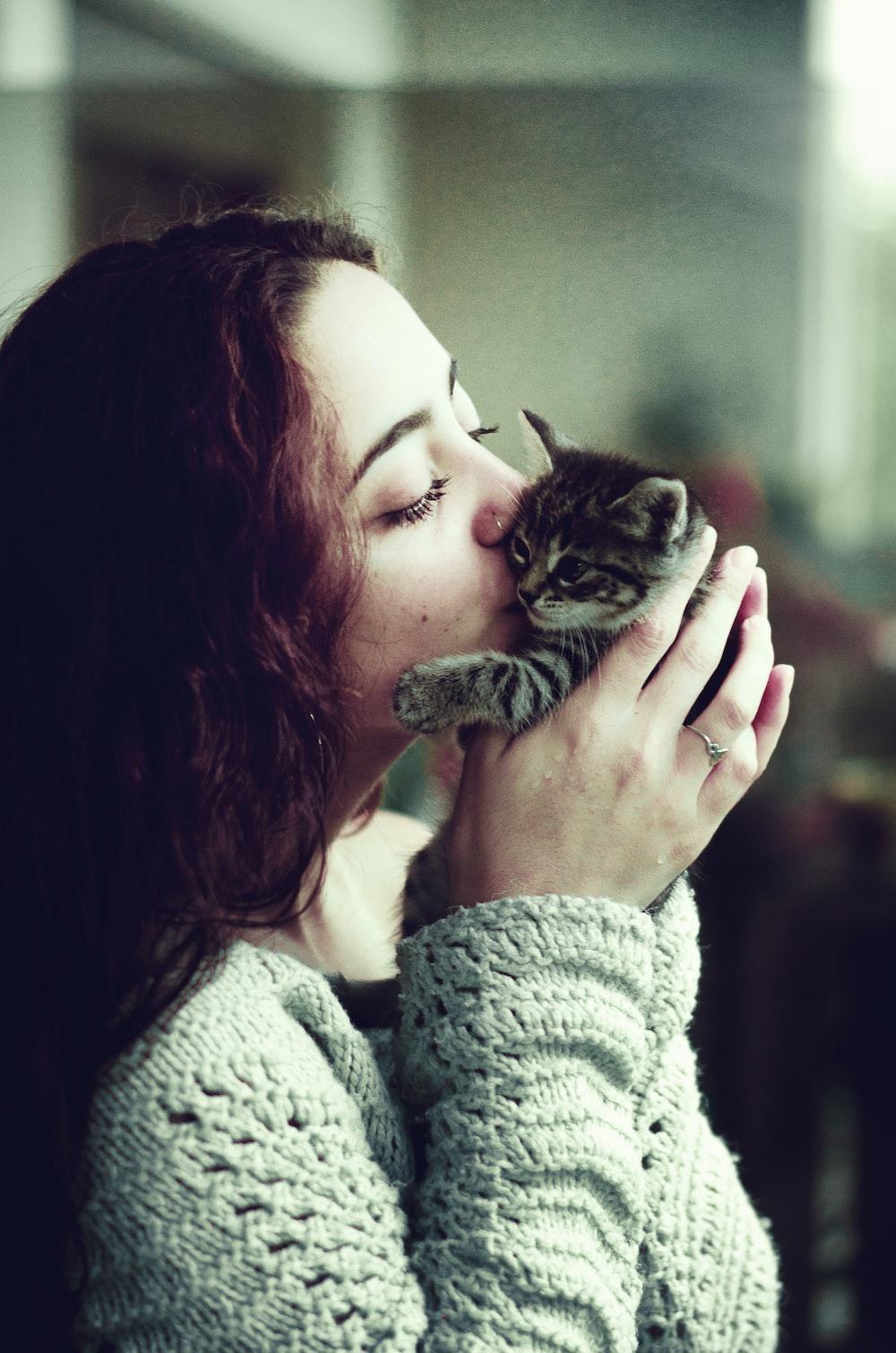 woman kissing gray tabby kitten