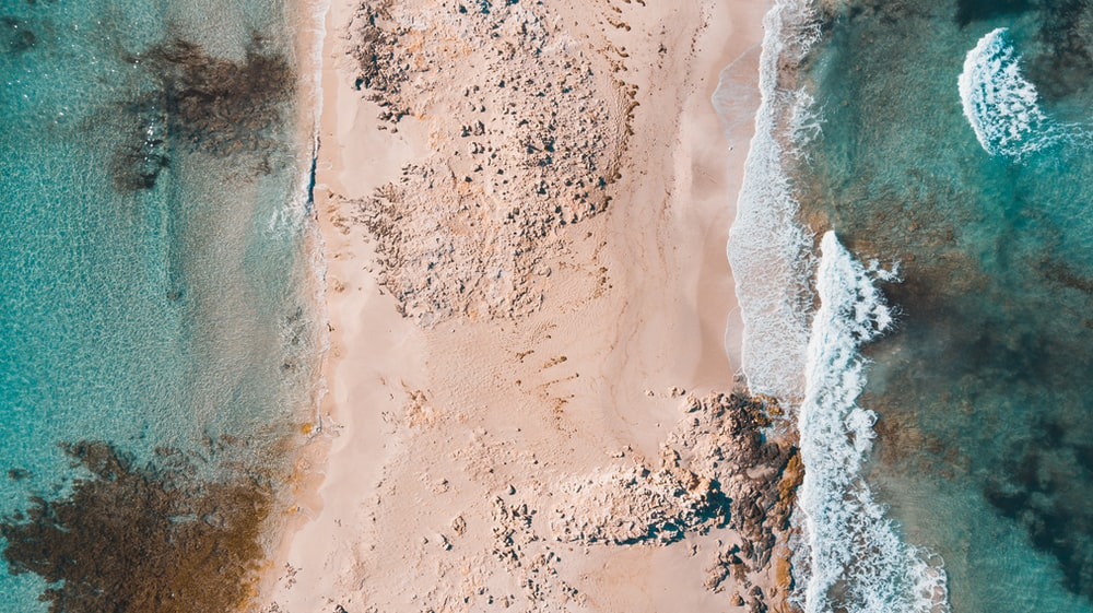 aerial photography of sand between sea