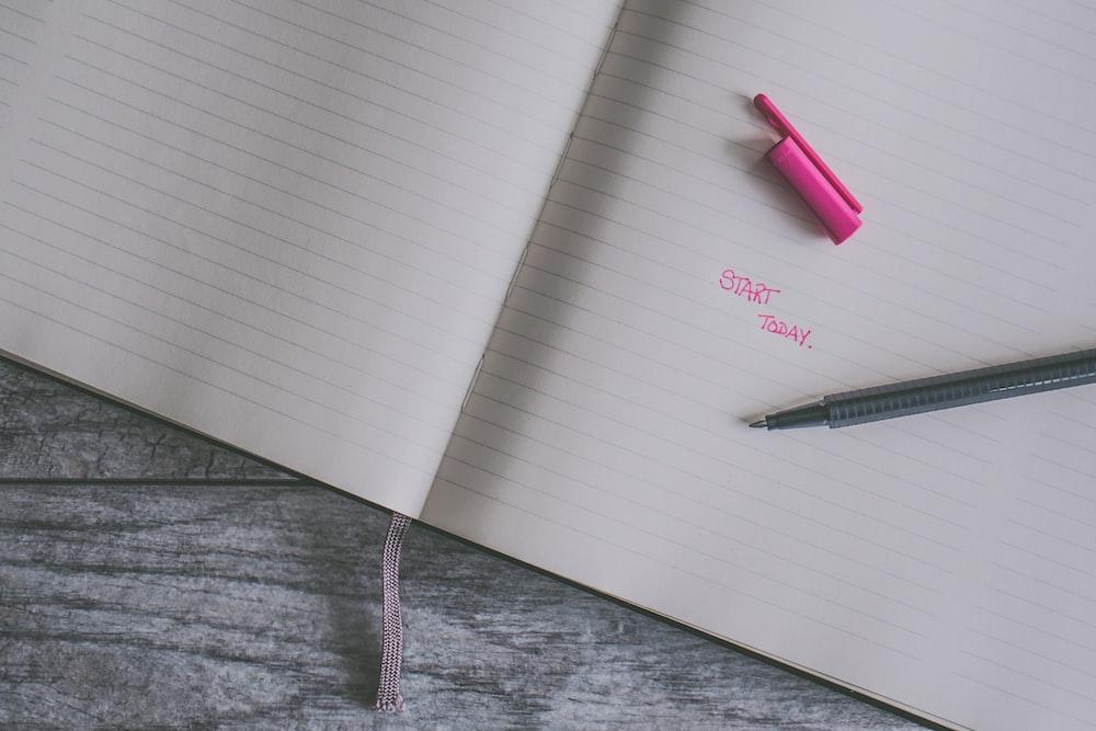 black pen on black line notebook