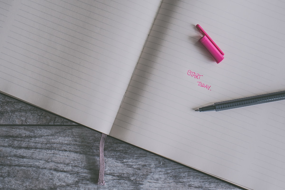 A notebook on a grey wood table.  There is an open pen with a pink cap.  In pink script the words START TODAY.