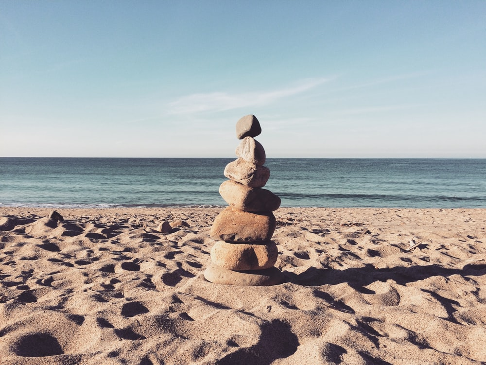 stacked stones on the sea shore during daytime