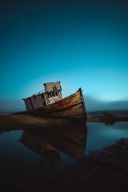 abandoned ship on seashore under sky with stars