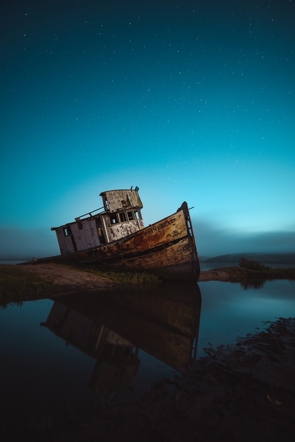 abandoned ship on seashore under sky with stars