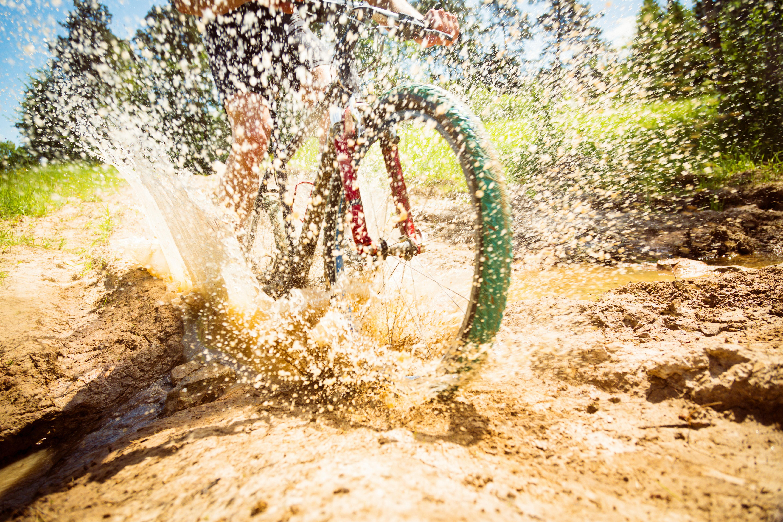 person riding bike on puddle with water splashing during daytime